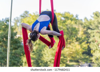 A lady in blue and black fitness outfit is hanging on a red ribbon is attempting to tied red ribbon on her legs.