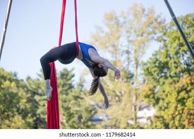 A lady in blue and black fitness outfit is dancing on a red ribbon