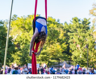 A lady in blue and black fitness outfit is hanging on a red ribbon while attaching red ribbon on her legs.