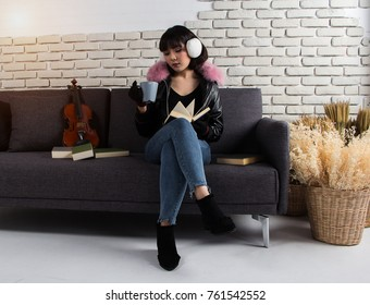 The lady with blue jean and leather jacket is sitting beside violin on sofa,read book in relax posing at living room.vintage warm light tone,blurry light around.