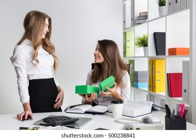 Lady boss is pleased with her subordinate who has given her a present. Concept of good relations in the team.