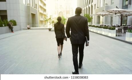 Lady boss walking by office building followed by male bodyguard, back view