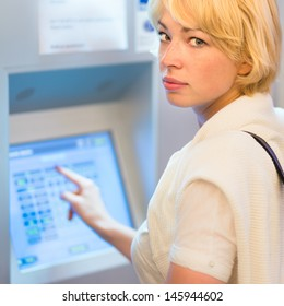 Lady buying a railway ticket at the automatic ticket vending machine with touch screen.