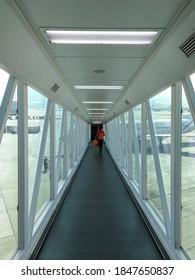Lady carry backpack & hand luggage, walking on jet bridge (jetway, jetwalk, airgate, gangway, aerobridge, airbridge, skybridge, airtube, or passenger boarding bridge (PBB) to board airplane