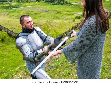 A lady in a chain mail hands a sword to her knight in armor. Knightly armor and weapon. Semi - antique photo.