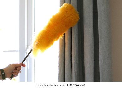 Lady cleaning around window and curtain pole with bright yellow fluffy duster on a stick