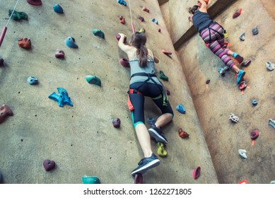 Lady Doing Extreme Sport Female Makes Hard Move on indoor Climbing Wall Sporty Clothing on Fitness Training Intense
