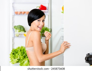 Lady eating near the opened fridge full of vegetables and fruit. Concept of healthy and dieting food