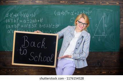 Lady educator in classroom prepare for new school year. Beginning of new school season. Woman teacher formal suit holds blackboard inscription back to school. Teacher welcomes new school year.