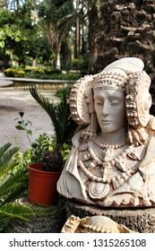 Lady of Elche bust in a garden.