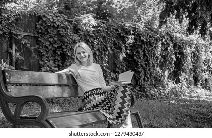Lady enjoy poetry in garden. Enjoy rhyme. Woman happy smiling blonde take break relaxing in garden reading poetry. Girl sit bench relaxing with book, green nature background. Romantic poem.