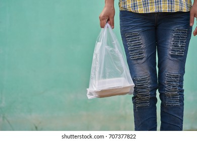lady in fashionable blue  ripped jeans , yellow and blue  plaid shirt stands in light green wall. she taking a plastic bag of packed lunch. concept is convenience