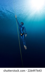 Lady free diver ascending from depth without fins. Free immersion discipline