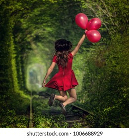 Lady Girl in red dress with red balloons is jumping at The Tunnel Of Love, Klevan', Ukraine. Green tunnel. Railway tunnel.