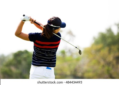 Lady gofer golf swing on course.
