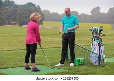 A lady golfer being taught to play golf by a Pro on a practice driving range.