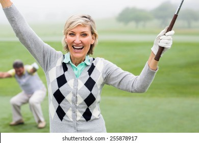 Lady golfer cheering at camera with partner behind on a foggy day at the golf course