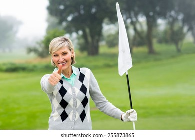 Lady golfer holding flag on a foggy day at the golf course
