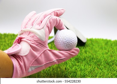 Lady golfer is holding golf ball on green grass background.