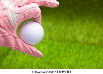 Lady golfer is holding white golf ball  on green grass background.