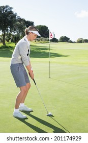 Lady golfer on the putting green at the eighteenth hole on a sunny day at the golf course
