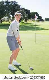 Lady golfer on the putting green at the eighteenth hole smiling at camera on a sunny day at the golf course