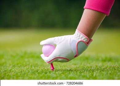Lady golfer placing her pink ball and tee into the ground on a golf course.