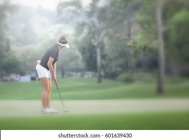 Lady golfer are set up to putting stroke.