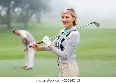 Lady golfer smiling at camera with partner behind on a foggy day at the golf course