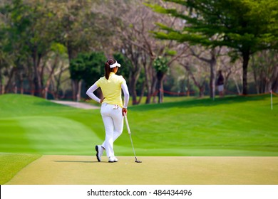 Lady golfer standing on the green.