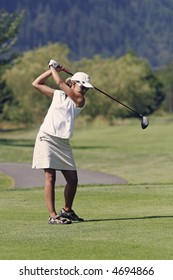 Lady golfer tees off with a driver