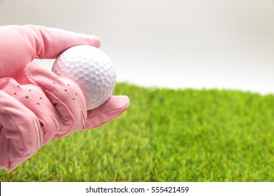 Lady golfer wears pink glove is holding golf ball on green grass background