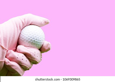 Lady golfer wears pink golf glove is holding golf ball isolated on pink background