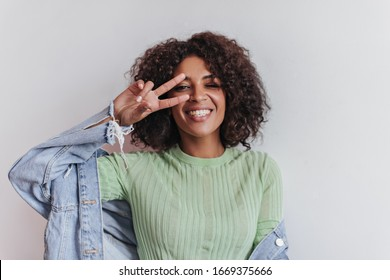 Lady in green t-shirt smiles and shows peace sign on white background. Cheerful woman in denim jacket laughing on isolated backdrop
