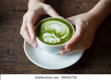 Lady hand holding a white cup of match Latte , Green Tea, on Wooden Background table.