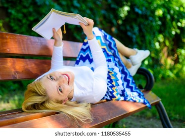 Lady happy face enjoy reading. Time for self improvement. Girl lay bench park relaxing with book, green nature background. Girl reading outdoors while relaxing on bench. Woman spend leisure with book.