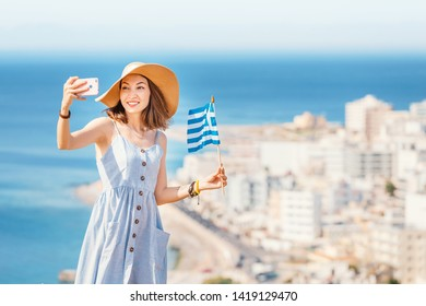 Lady in hat with greek flag taking slefie on her smartphone at the hill top to the mediterranean seacoast and rhodes town