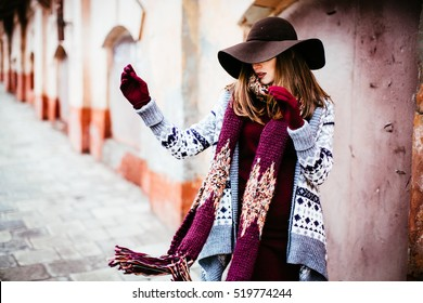 lady in the hat   throws a  red  scarf aside
