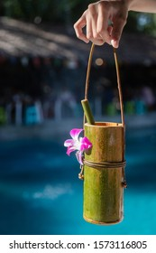 Lady have holding a Bamboo natural cup with small bamboo tube, docorate with purple flower, tie together with vine. Blue pool and market on background
