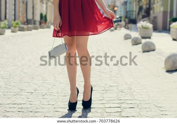 彼氏とデートしてる女性。彼女は赤い美しいショートドレスを着て、黒いハイヒールを履き、手提げ袋を持っている。通りで女性の脚をハイヒールでつり写した写真。