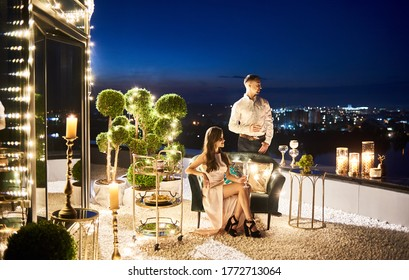 Lady having romantic date with boyfriend at rooftop restaurant. Attractive girl and gentleman holding glasses of champagne and enjoying night city view. Concept of love, relationships and luxury.