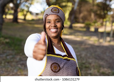 lady with her thumbs up while looking straight into the camera with a beautiful smile.