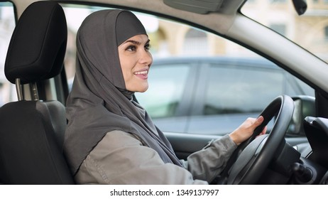 Lady in hijab looking rear view mirror sitting in auto, city transport, license