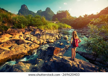 Lady hiker standing on the rock and enjoying view of the river