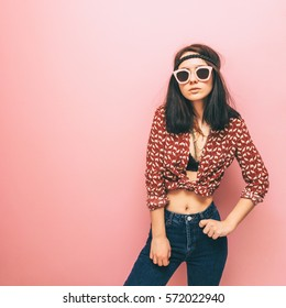 Lady in a hippie style is in fashion pose. Trendy clothes. Pastels and minimalism.