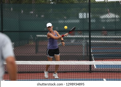 a lady hits a pickleball as she plays in a tournament