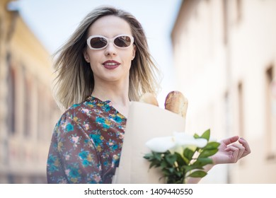 Lady and homemaker. Woman on the street holding bag with food.