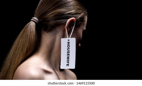Lady with housewife label on ear against dark background, place of women, sexism