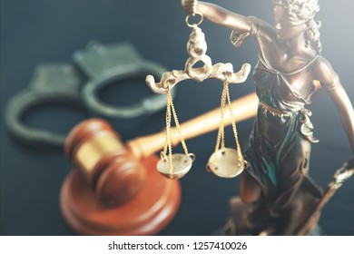 lady justic with judge and handcuffs on table