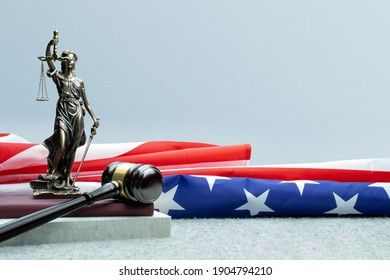 Lady justice, judge gavel and books in front of a usa flag.